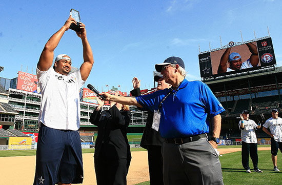 Dallas Cowboys DL Jason Hatcher holds up the winners trophy after winning the competition.